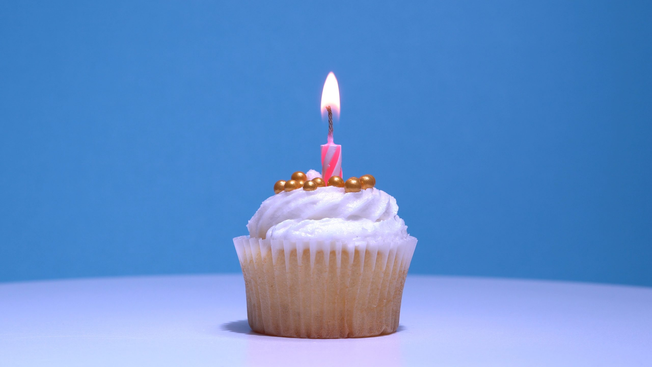 Cupcake,With,Single,Birthday,Candle,Burning,And,Sugar,Sprinkles,Icing